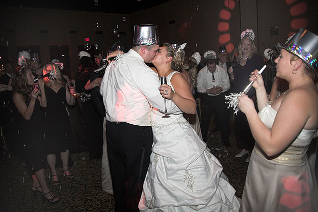 New Year's wedding reception with bride & groom kissing in the new year!